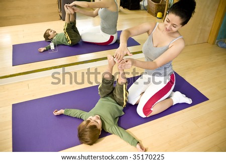 Young hispanic woman and child doing pilates in a gym