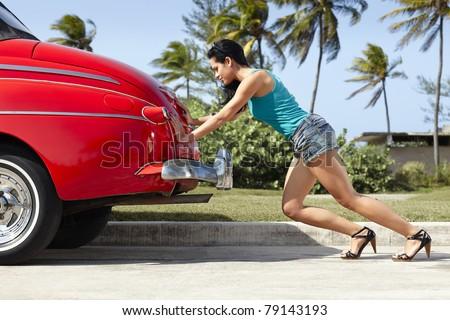 young hispanic woman pushing broken down red convertible vintage car. Horizontal shape, full length, side view - stock photo