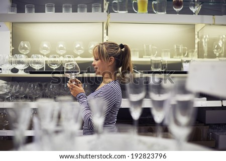 young hispanic woman shopping for furniture, glasses, dishes and home decor in store - stock photo