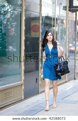 Young Hispanic woman walking down city street