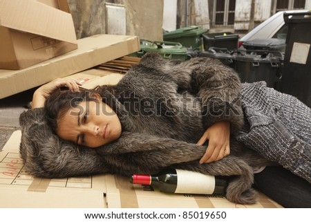 young hobo woman lying on city pavement with bottle of wine - stock photo