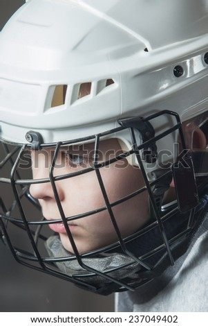 Young hockey player in a white helmet - stock photo
