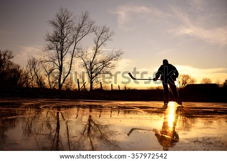 Young hockey player on natural ice during calm winter sunset