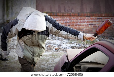 Young hooligan smashing windshield - stock photo