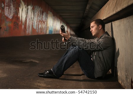 young hooligan with baseball bat sitting in tunnel - stock photo