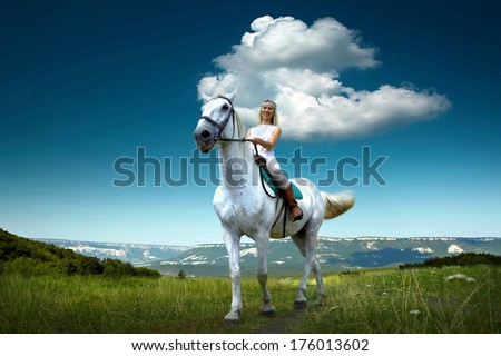 Young horsewoman riding on white horse, outdoors view - stock photo