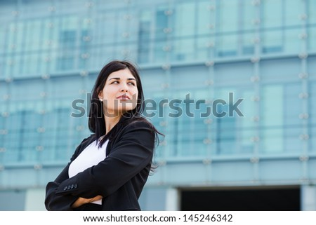 Young hot businesswoman with crossed arms in front of a building with a copyspace to the left - stock photo