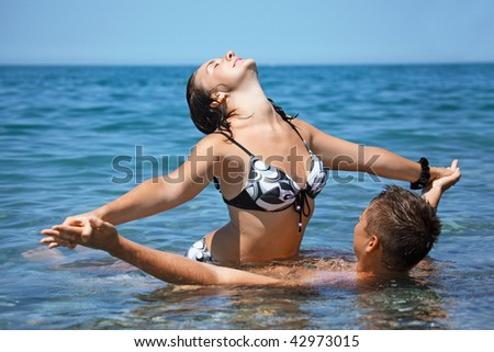 young hot woman sitting astride man in sea near coast, Having joined hands - stock photo