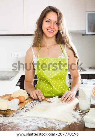 Young housewife cooking with dough at home kitchen - stock photo