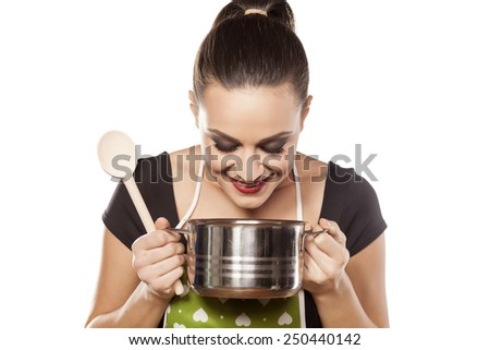 young housewife enjoys the smell of her food - stock photo