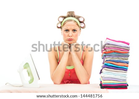 Young housewife has got a lot of  laundry for ironing and she is very angry because of it,Too much laundry - stock photo