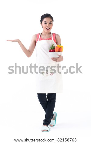 Young housewife holding a bowl of vegetable in one hand and empty other hand holding your product with feeling wonderful