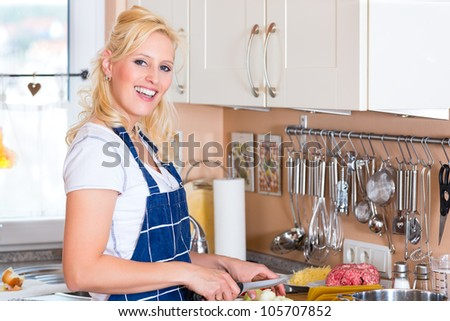 Young Housewife is cooking and chopping onions for lunch or dinner - stock photo