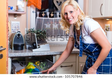 Young housewife is doing the dishes with dishwasher - stock photo