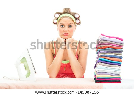 Young housewife is unhappy because she has got a lot of laundry for ironing,Unhappy housewife - stock photo