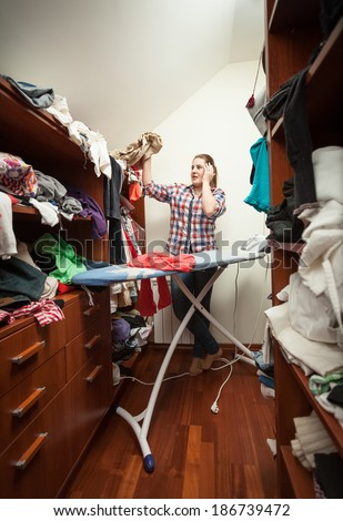 Young housewife looking at not ironed clothes at wardrobe - stock photo
