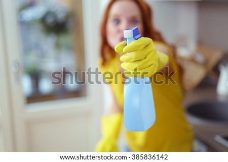 Young housewife squirting the camera with detergent in a spray bottle, focus to her gloved hand