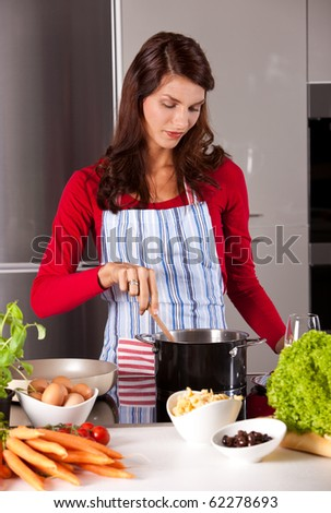Young housewife stirring in a pan on the stove - stock photo