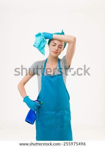 young housewife tired after cleaning, standing against white background - stock photo