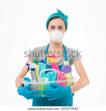 young housewife wearing protection mask, holding cleaning supplies against white background - stock photo