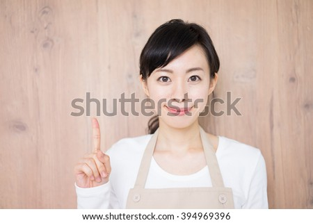 young housewife with apron against wooden wall - stock photo