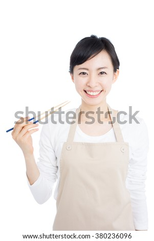 young housewife with apron holding long chopsticks, isolated on white background - stock photo