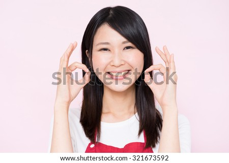 young housewife with apron showing OK gesture against pink background - stock photo