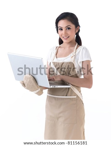 Young housewife with kitchen protective glove working with laptop - stock photo