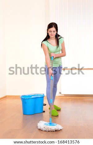 Young housewife with  mop in room  - stock photo