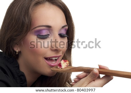 Young housewife with the spoon testing food