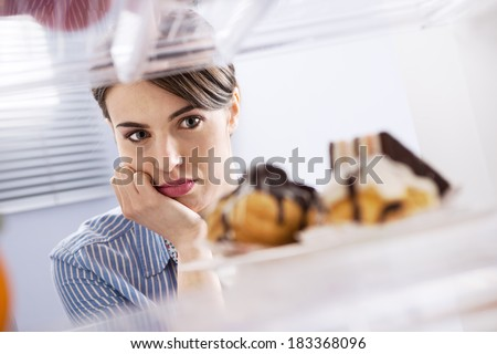 Young hungry woman in front of refrigerator craving chocolate pastries. - stock photo