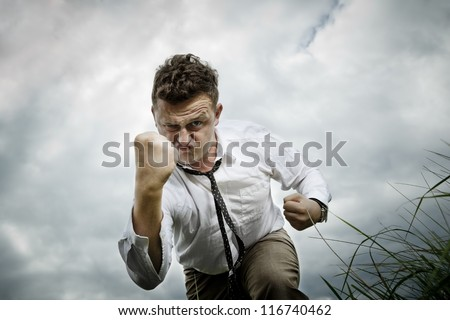 Young hunk shows his fist. He is strong and determined to fight. It has a stupid look on his face, so it's not so dangerous. - stock photo
