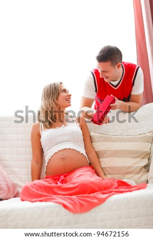 Young husband making present to pregnant wife - stock photo