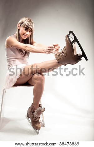 Young ice skater putting on skate - stock photo
