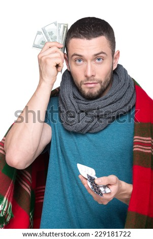 Young ill man is holding a money and pills and looking at the camera. - stock photo