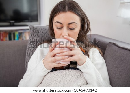 Young ill woman,drinking cup of hot tea, lying at home