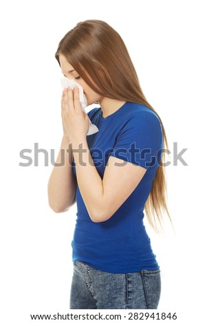 Young ill woman using a tissue. - stock photo