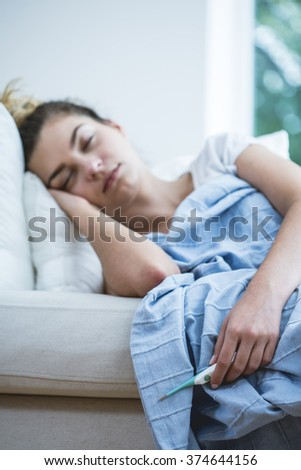 Young ill woman with temperature in bed