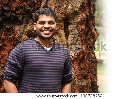 Young indian adult smiling looking at camera and expressing joy and happiness. The photo is with space for text on the right.