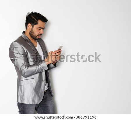 Young Indian business man working on his Mobile against a white background - stock photo
