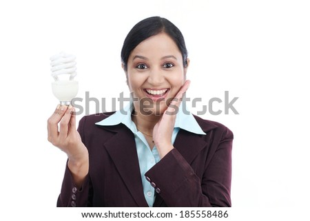 Young Indian business woman holding electric bulb against white background