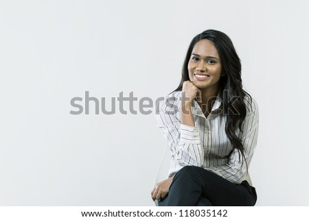 Young Indian business woman sitting on a chair. - stock photo