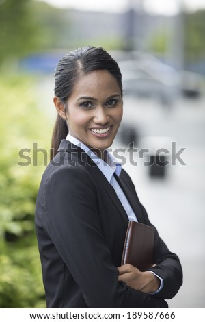 Young Indian business woman with standing outside an office building.