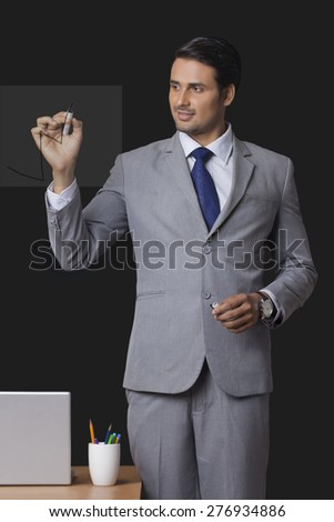 Young Indian businessman drawing graph on transparent screen