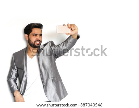 Young Indian Businessman photographing of himself against the white background