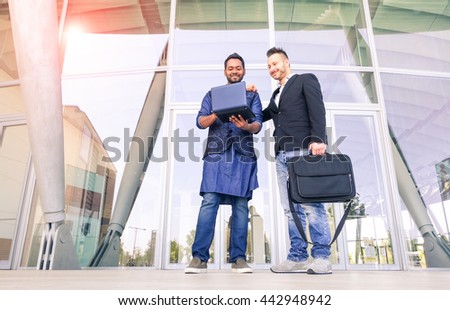 Young indian businessman showing work-plan at colleague - Cheerful men with laptop  standing outside business building - Concept of global market and multiethnic cultures working everyday together - stock photo