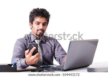 young indian businessman using cell phone while working on the laptop, Indian businessman working on the laptop isolated on white - stock photo