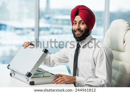 Young indian businessman with suitcase full of money. - stock photo