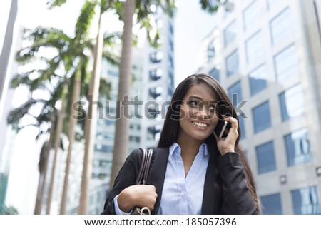 Young Indian businesswoman standing outside using mobile phone - stock photo