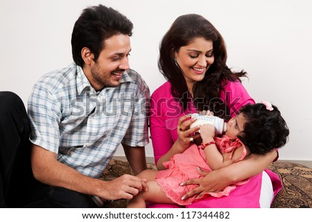 young Indian couple relaxing and enjoying with their daughter - stock photo